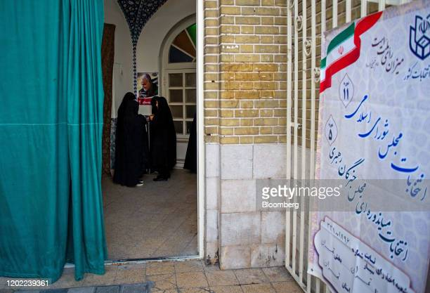 Iranians vote for a new parliament at a polling station which displays a photograph of killed Iranian GeneralQassem Soleimaniduring the general...