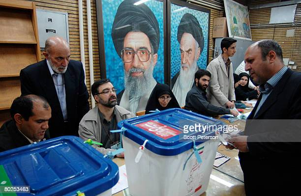 Iranians vote in front of posters of Iran's two supreme leaders Ayatollah Sayed Ali Khamenei and Ayatollah Ruhollah Khomeini in elections for the 8th...