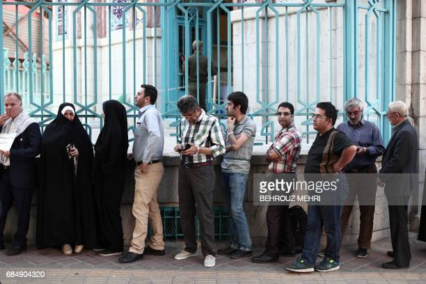 TOPSHOT Iranians wait in a queue for the opening of the polling station to cast their ballots for the presidential elections in Tehran on May 19 2017...