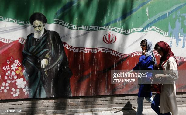Iranians walk by mural painting of the founder of the Islamic Republic Ayatollah Ruhollah Khomeini on the wall of the former US embassy in the...