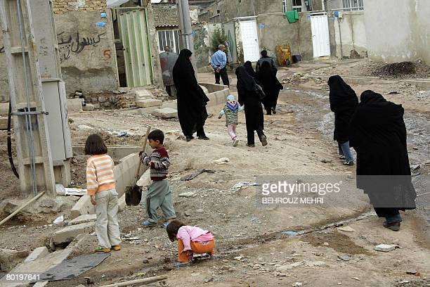 Iranians walk in a poor neighbourhood in the town of Ghaleh Hassan Khan on the southwestern outskirts of Tehran on March 11 2008 High inflation...