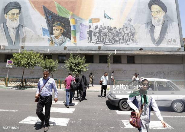 Iranians walk near a billboard bearing portraits of late Ayatollah Ruhollah Khomeini and Iran's Supreme Leader Ayatollah Ali Khamenei in Tehran on...