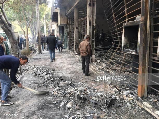 Iranians walk past a charred bank that was set ablaze by protesters during a demonstration against a rise in gasoline prices in the central city of...