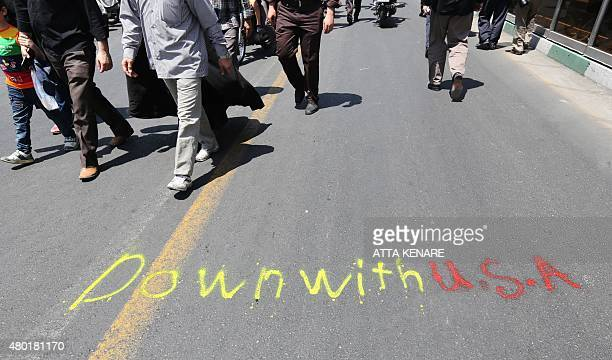 Iranians walk past a graffiti on a street during a demonstration to mark the Quds International day in Tehran on July 10 2015 AFP PHOTO / ATTA KENARE