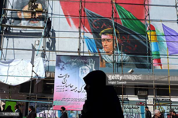 Iranians walk past a mural of Iran's supreme leader, Ayatollah Ali Khamenei, as workers put the final touches to it at Enghelab square on February...