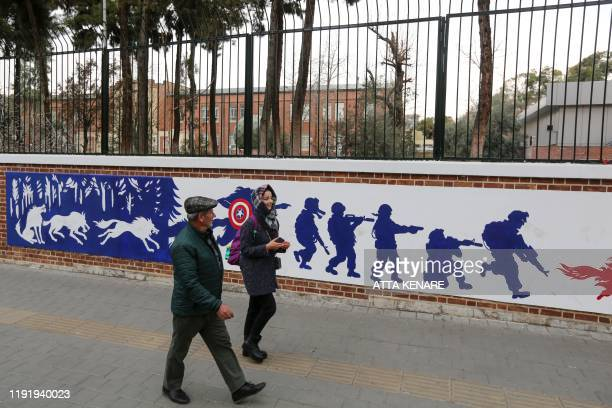Iranians walk past a mural painted on the walls of the former US embassy in the capital Tehran on January 4 one day after Soleimani and other members...