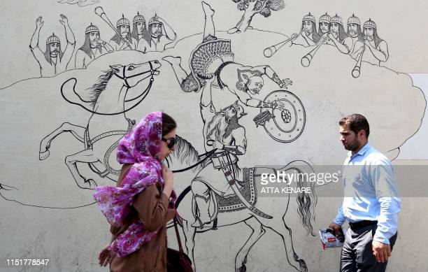 Iranians walk past a mural painting illustrating ancient Persian poetry in the Iranian capital Tehran on June 25, 2019. - Iran's President Hassan...