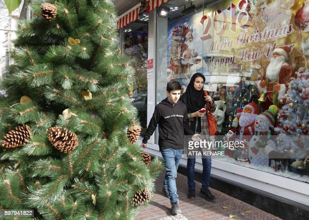 Iranians walk past Christmas decorations in a street in the capital Tehran on December 24 on Christmas eve / AFP PHOTO / ATTA KENARE