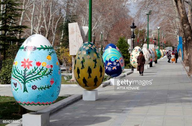 Iranians walk past large decorated eggs displayed at the Mellat park during an event organised by the municipality of Tehran on March 16 ahead of the...