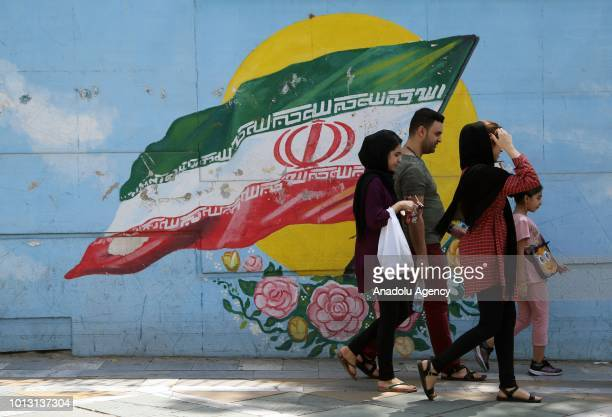 Iranians walk past mural painting as daily life continues despite of the US sanctions against Iran on August 08 2018 in Tehran Iran