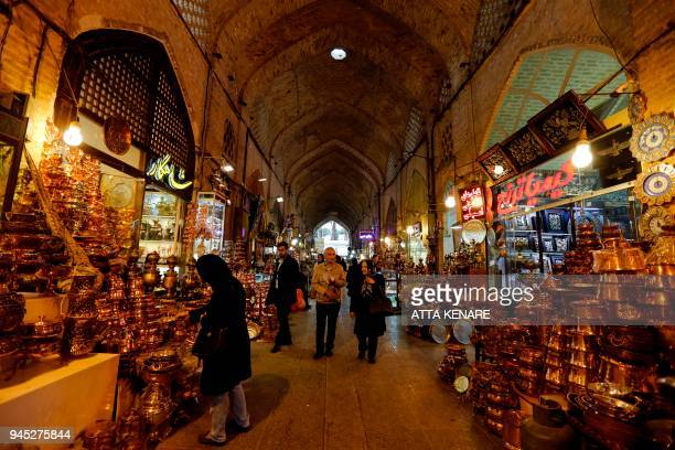 Iranians walk past shops in the Bazaar in Isfahan on April 12, 2018. / AFP PHOTO / ATTA KENARE