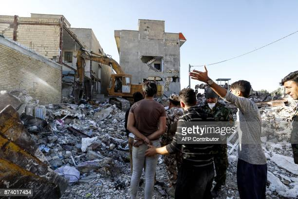Iranians watch as a digger goes through the debris of damaged buildings in the town of Sarpole Zahab in Iran's western Kermanshah province near the...