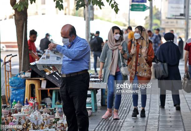 Iranians wear face masks as a measure against the Covid-19 coronavirus, in a street in the capital Tehran, on July 7, 2021.