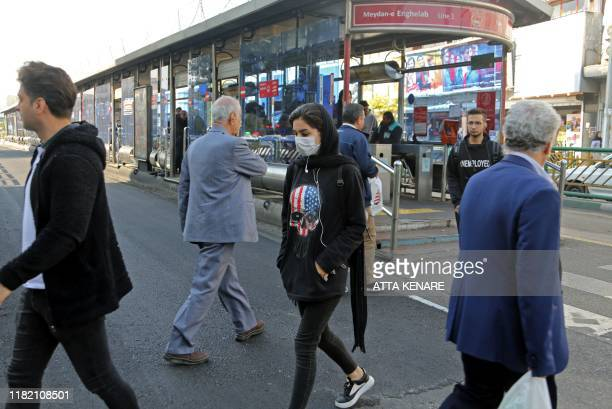 Iranians wear masks to help guard against dangerous levels of air pollution as they walk in the centre of the smogfilled capital Tehran on November...