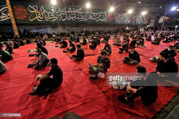 TOPSHOT Iranians wearing face masks against the Covid19 coronavirus attend Laylat alQadr prayers one of the holiest nights during the Muslim fasting...