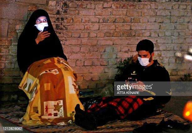 TOPSHOT Iranians wearing face masks against the Covid19 coronavirus attends Laylat alQadr prayers one of the holiest nights during the Muslim fasting...
