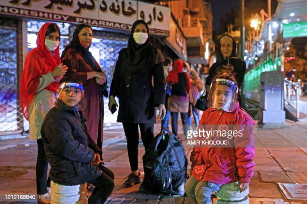 Iranians wearing maks against the coronavirus Covid-19 gather outside their buildings after an earthquake was felt in the capital Tehran on May 7,...