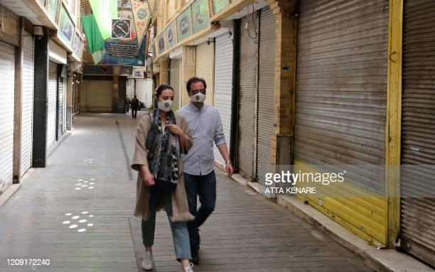 Iranians wearing protective face masks against the novel coronavirus walk along an alley of a closed indoors market in the capital Tehran on April 5...
