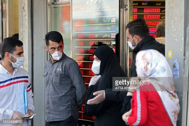 Iranians, wearing protective masks without observing social distancing, queue outside a money exchange office in the capital Tehran on May 9 during...