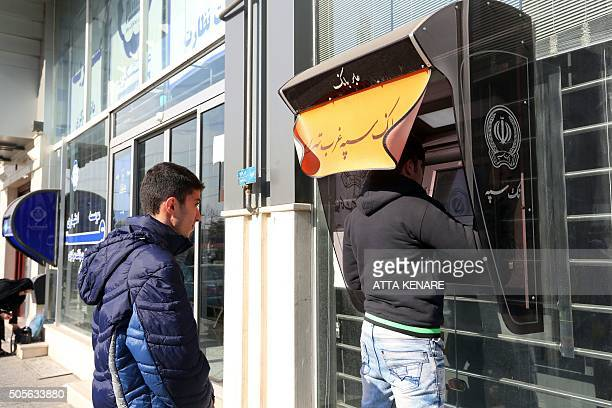 Iranians withdraw money from an ATM machine at a Bank Sepah in the capital Tehran on January 19 2016 Iran will receive $32 billion of unfrozen assets...
