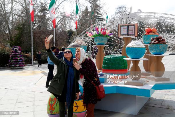 Iranians women take a selfie with decorations displayed at the Mellat park during an event organised by the municipality of Tehran on March 16 ahead...