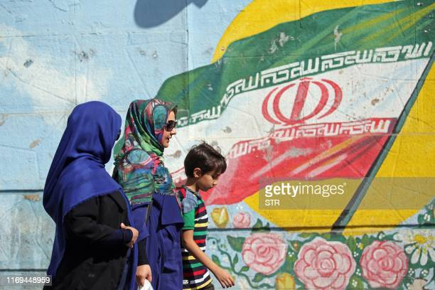 Iranians women walk past a mural of depicting the Iranian national flag in a street in capital Tehran September 19 2019 Foreign Minister Mohammad...