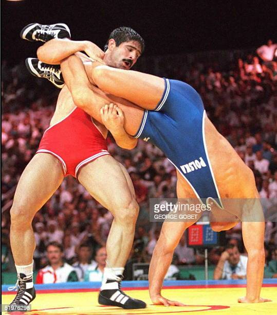Iran's Abbas Jadidi throws Poland's Marek Garmulewicz during their semifinals of the men's Olympic freestyle 100kg wrestling 31 July at the Georgia...