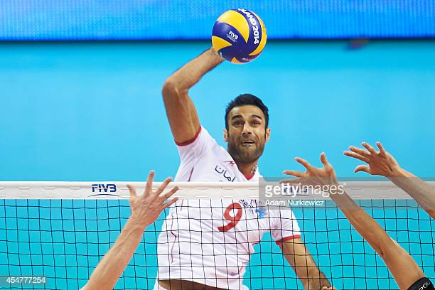 Iran's Adel Gholam spikes the ball during the FIVB World Championships match between Belgium and Iran at Cracow Arena on September 6, 2014 in Cracow,...