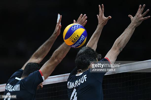 Iran's Adel Gholami and Iran's Mir Saeid Marouflakrani attempt to block the ball at the net during the men's qualifying volleyball match between Iran...