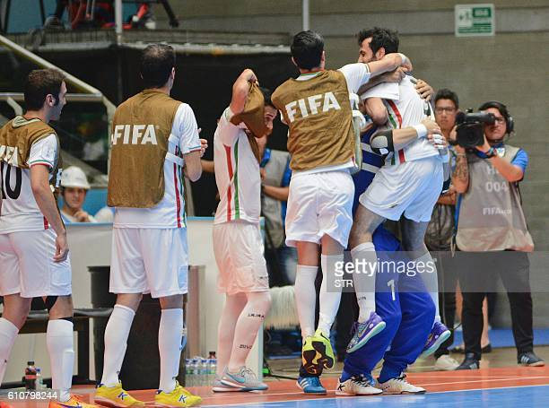 Iran's Ahmad Esmaeilpour celebrates with teammates his goal scored against Russia during their Colombia 2016 FIFA Futsal World Cup semifinal match in...