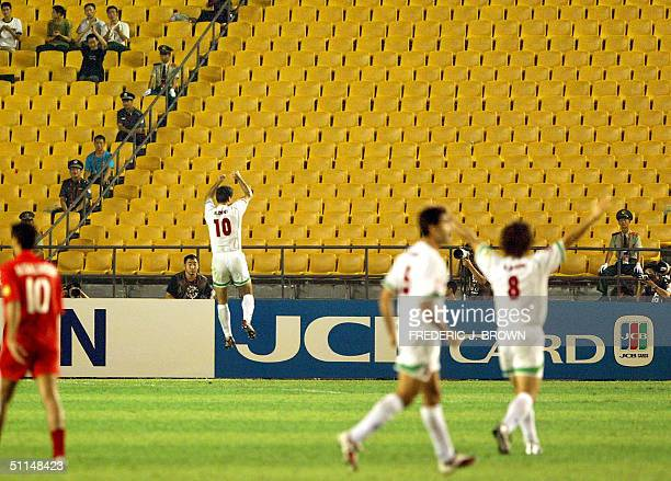 Iran's Ali Daei celebrates for nearempty stands as Bahrain's Mohamed Salmeen and Iran's Rahman Rezaei and Ali Karemi react at Beijing's Worker's...