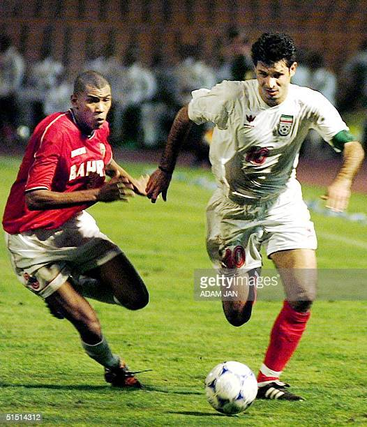 Iran's Ali Daei vies for the ball against Bahrain's Abdulla A Rahman during their Group A qualifying 2002 World Cup soccer match in Manama 21 October...