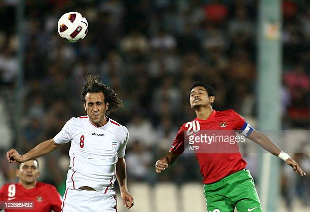 Iran's Ali Karimi jumps to head the ball with Indonesia's Bambang Pamungkas during their 2014 World Cup Asian zone qualifying football match at Azadi...