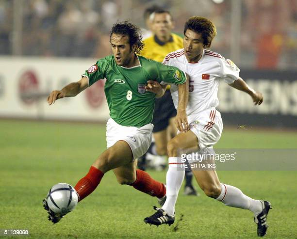 Iran's Ali Karimi tries to get the ball pass China's defender Zheng Zhi during the Asian Cup semifinal match 03 August 2004 in Beijing China and Iran...