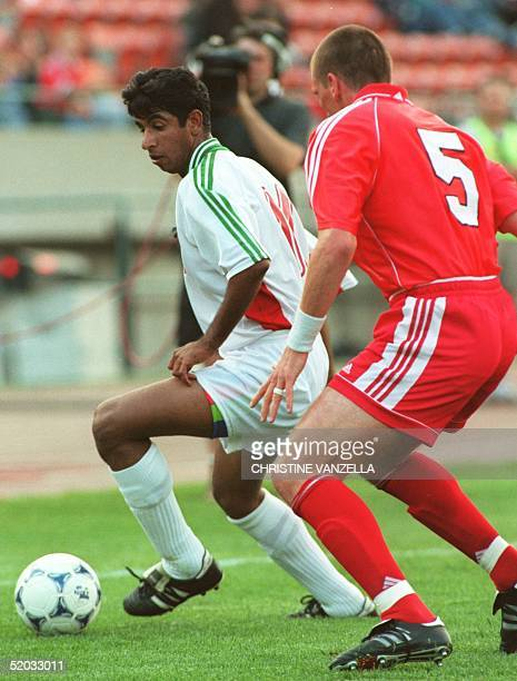 Iran's Ali Mousavi dribbles around Canada's Jason Devos in Canada Cup soccer action at Commonwealth Stadium in Edmonton 04 June 1999