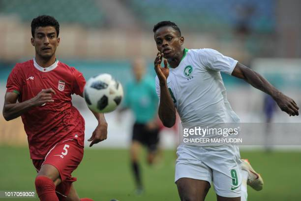 Iran's Alireza Arta fights for the ball with Saudi Arabia's Haroune Moussa Camara during the men's football Group F match between Iran and Saudi...
