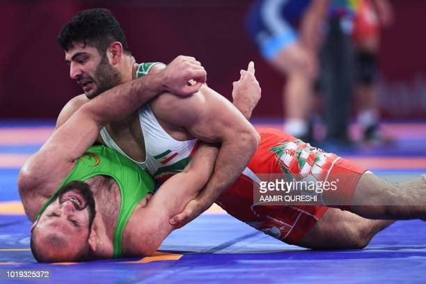Iran's Alireza Karimimachiani competes with Uzbekistan's Magomed Ibragimov in the men's wrestling freestyle 97kg semifinal at the 2018 Asian Games in...