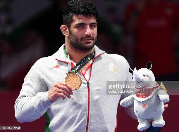 Iran's Alireza Karimimachiani poses with his gold medal at the men's freestyle 97kg wrestling medal ceremony at the 2018 Asian Games in Jakarta on...
