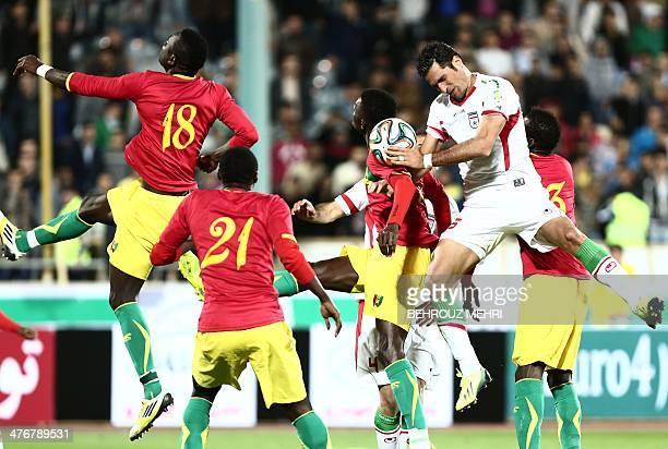 Iran's Amir Hossein Sadeghi vies for the ball with Boubacar Fofana and Djibril Tamsir Paye of Guinea during their international friendly football...