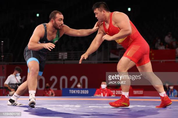 Iran's Amir Hossein Zare wrestles China's Deng Zhiwei in their men's freestyle 125kg wrestling bronze medal match during the Tokyo 2020 Olympic Games...
