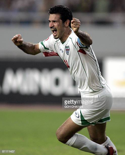 Iran's captain Ali Daei celebrates after his teammate Mohammed Nosrati scored the equalizer goal during the Asian Cup group D match between Iran and...
