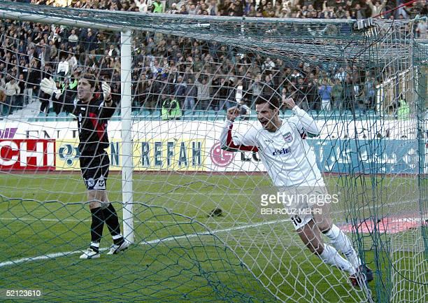 Iran's captain Ali Daei jubilates after scoring a goal as Bosnian goalkeeper Kenan Hasagic reacts during their friendly match at Tehran's Azadi...
