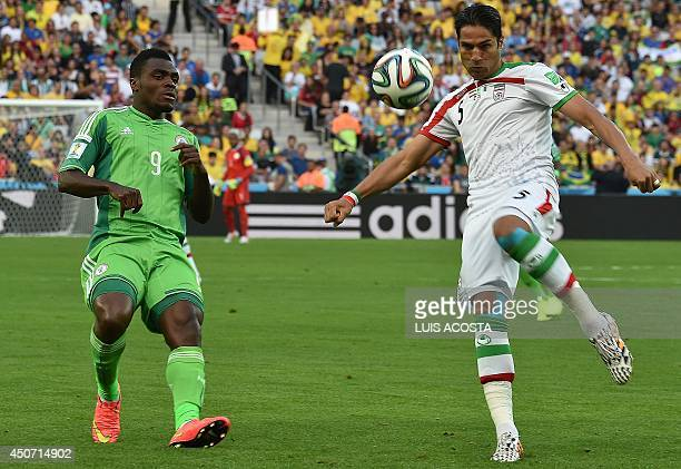 Iran's defender Amir Hossein Sadeqi challenges Nigeria's forward Emmanuel Emenike during the Group F football match between Iran and Nigeria at the...
