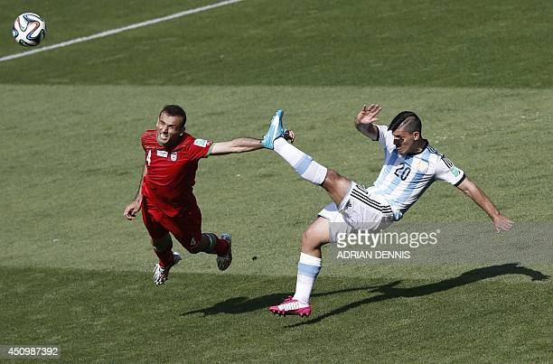Iran's defender Jalal Hosseini and Argentina's forward Sergio Aguero vie during the Group F football match between Argentina and Iran at the Mineirao...