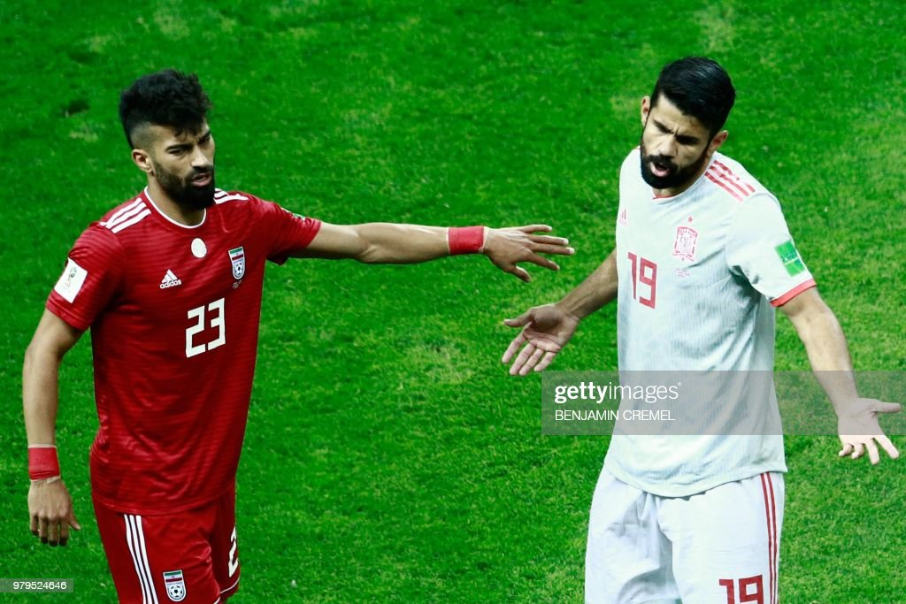 Iran's defender Ramin Rezaian (L) gestures as Spain's forward Diego Costa (R) reacts during the Russia 2018 World Cup Group B football match between Iran and Spain at the Kazan Arena in Kazan on June 20, 2018. (Photo by BENJAMIN CREMEL / AFP) / RESTRICTED