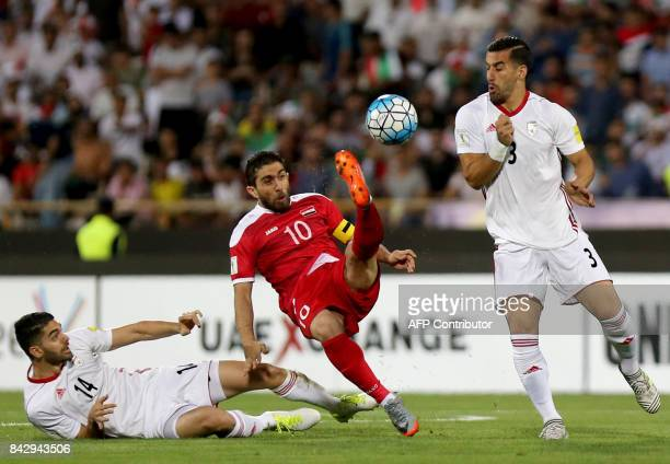 Iran's Ehsan Hajsafi and Ali Karimi fight for the ball against Syria's Firas Mohamad Alkhatib during the FIFA World Cup 2018 qualification football...