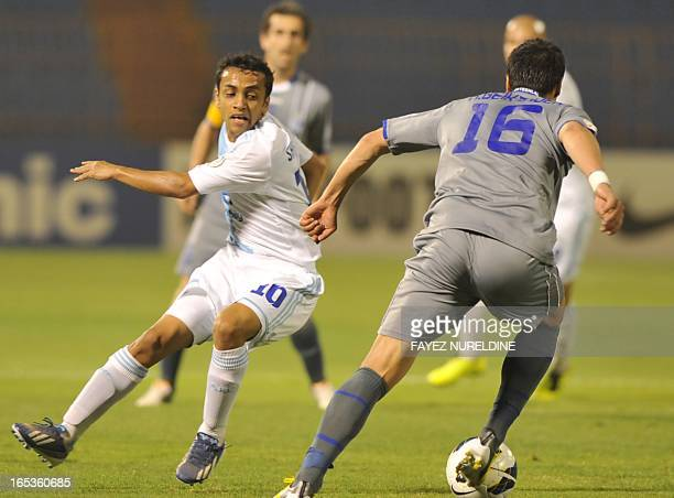 Iran's Esteghlal player Hashem Beikzadeh dribbles past Saudi's al-Hilal player Mohammed Shalhoub during their AFC Champions League group D football...