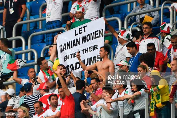 Iran's fans hold up a banner reading Let Iranian women enter theirs stadiums as they celebrate after the final whistle of the Russia 2018 World Cup...