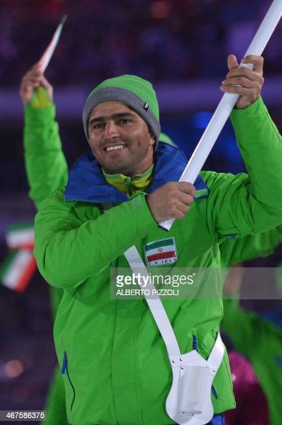 Iran's flag bearer alpine skier Hossein SavehShemshaki leads his national delegation during the Opening Ceremony of the 2014 Sochi Winter Olympics at...