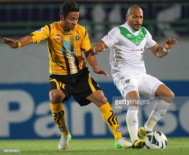 Iran's Foolad Sepahan midfielder Amin Jahanalian fights for the ball with Saudi's Al-Ahli Brazilian midfielder Victor Simoes De Oliveira during their...